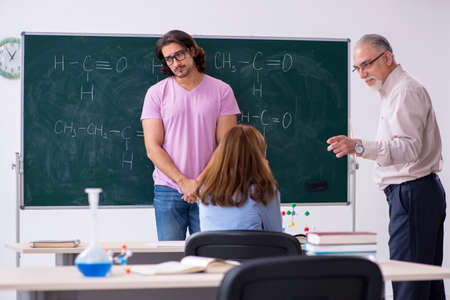 Old chemist teacher and two students in the classroom