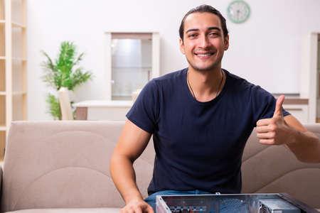 Young man repairing computer at home