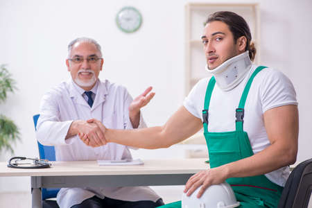 Young male contractor visiting old doctor