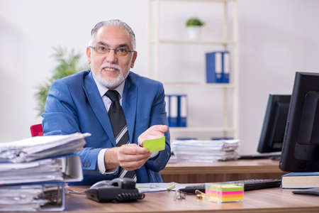 Old male employee and excessive work in the office Zdjęcie Seryjne