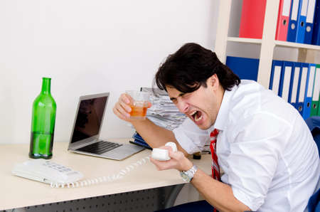 Young businessman employee drinking in the office Reklamní fotografie