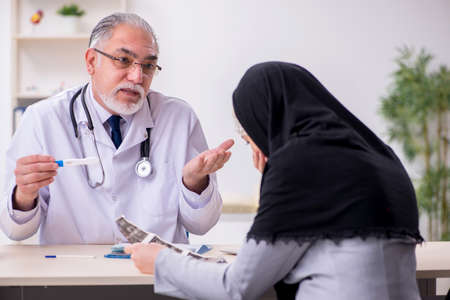 Arab woman visiting experienced doctor Stock Photo