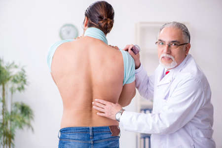 Young back injured man visiting experienced male doctor 写真素材