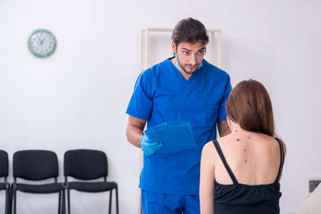 Young woman visiting male doctor dermatologist Imagens