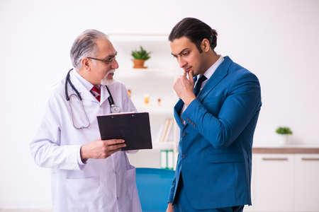 Young businessman meeting with old doctor Zdjęcie Seryjne