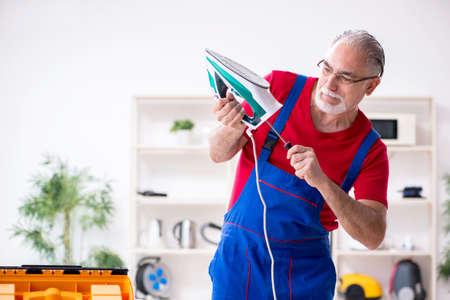 Old male contractor repairing iron indoors Stockfoto