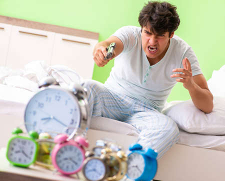 Young man having trouble waking up in early morning