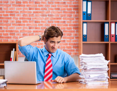 Young employee with excessive work sitting at the office Stock fotó