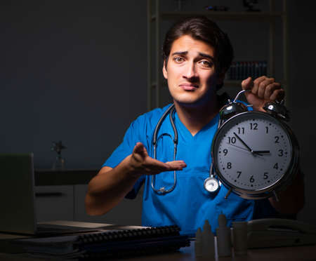 Young handsome doctor working night shift in hospital