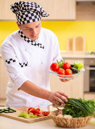 Young professional cook preparing salad at kitchen Stok Fotoğraf