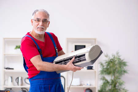 Old male contractor repairing air-conditioner indoors