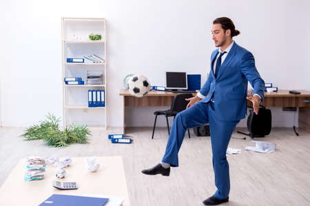 Young male employee playing football in the office Banque d'images