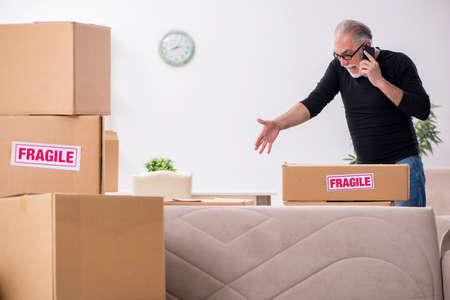 Vieux déménageur professionnel masculin faisant la relocalisation à la maison