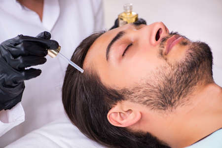 Young man visiting female beautician in hair transplantation con