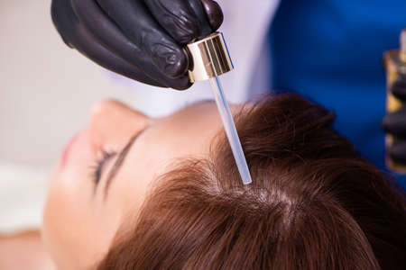 Young woman visiting male beautician in hair transplantation con