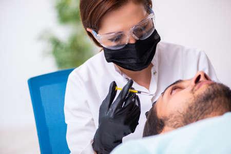 Young man visiting beautician in hair transplantation concept