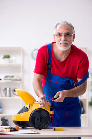 Old male contractor repairing vacuum cleaner indoors