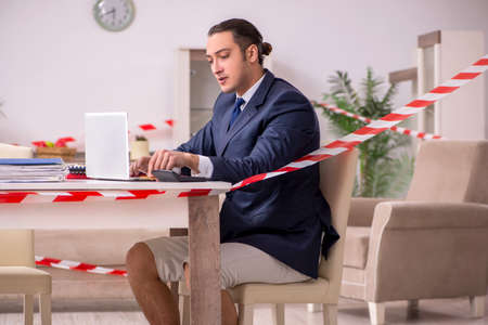 Young male employee working at home during pandemic disease