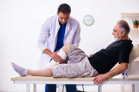Old injured man visiting young male doctor traumatologist
