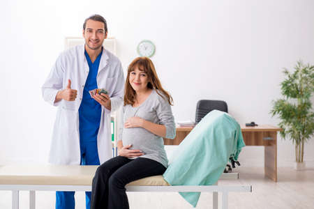 Young pregnant woman visiting male doctor gynecologist