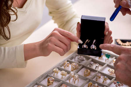 Young woman visiting old male jeweler 版權商用圖片