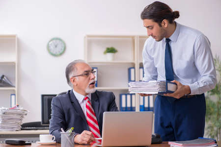 Old boss and young male employee in the office