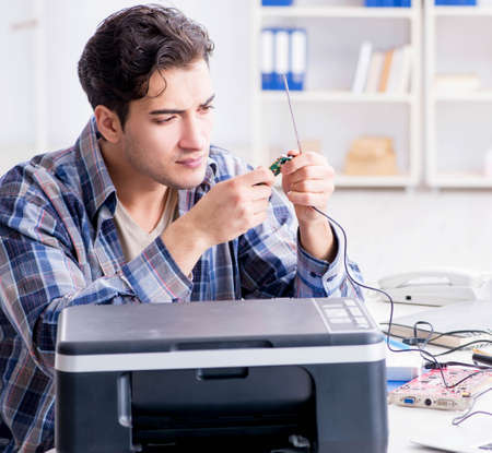 Hardware repairman repairing broken printer fax machine Standard-Bild