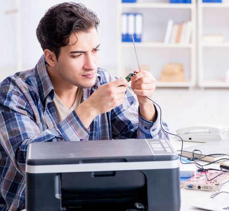 Hardware repairman repairing broken printer fax machine Stock Photo
