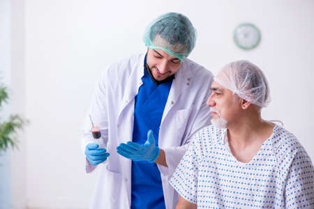 Old man visiting young male intern doctor