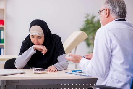Arab woman visiting experienced doctor Фото со стока