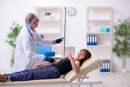 Young woman visiting old male doctor Фото со стока