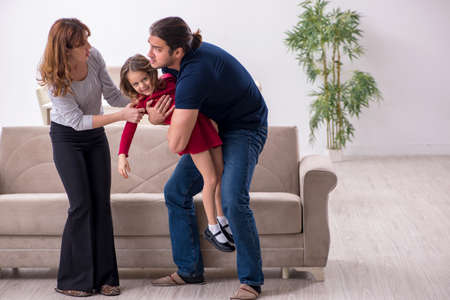 Young couple and their daughter in family conflict concept