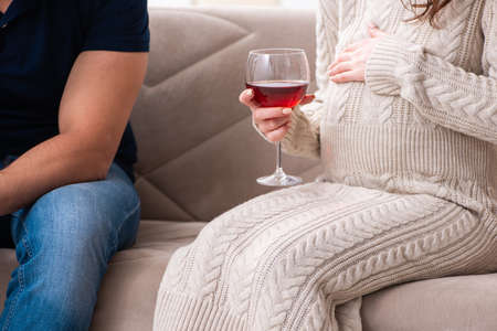 Man and pregnant woman in the alcoholism concept