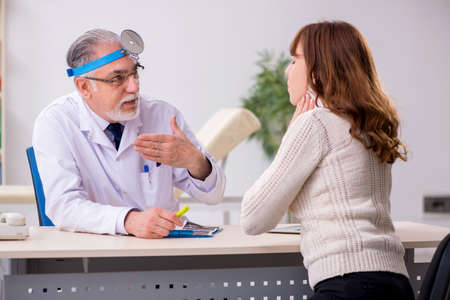 Young woman visiting old male doctor otorhinolaryngologist