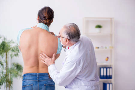 Young back injured man visiting experienced male doctor Фото со стока