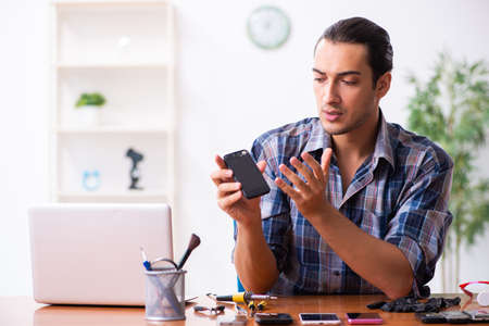 Young male technician repairing mobile phone