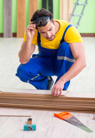 Professional contractor laying flooring at home Standard-Bild
