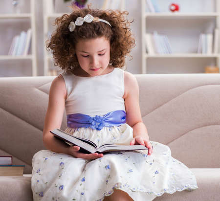 Little pretty girl reading books at home