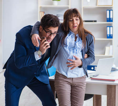 Pregnant woman struggling in the office and getting colleague he Banque d'images