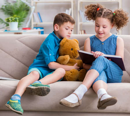 Two kids reading books at home