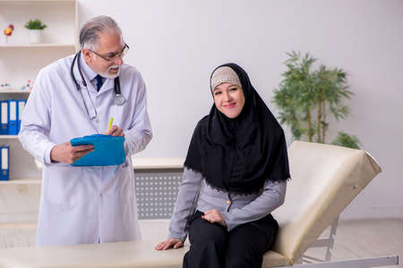 Arab woman visiting experienced doctor 스톡 콘텐츠
