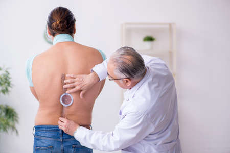 Young back injured man visiting experienced doctor