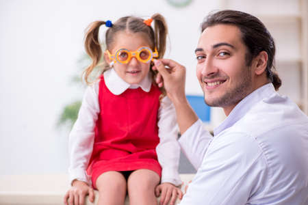 Small girl visiting young male doctor oculist