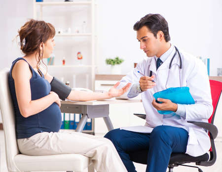 Young doctor checking pregnant womans blood pressure