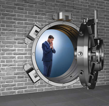 Businessman concerned about theft at banking vault door