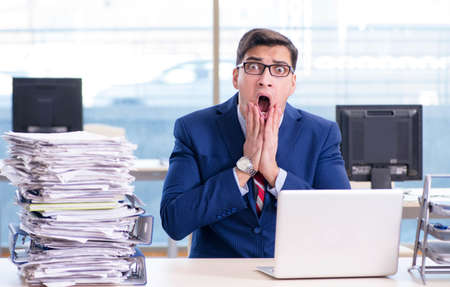 Businessman workaholic struggling with pile of paperwork Imagens