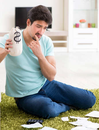 Young man struggling with personal finance and bills Imagens