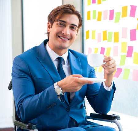 Young handsome man in wheelchair with many conflicting prioritie