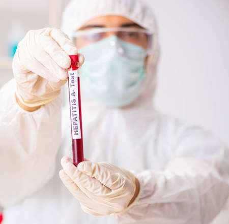 Young handsome lab assistant testing blood samples in hospital