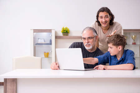 Grandfather learning new technology from son and grandson